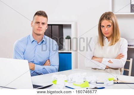 Angry businesswoman and businessman are sitting in their office.