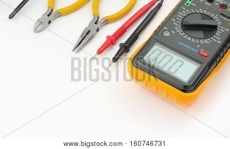 Multimeter probes needle nose pliers wire cutters screwdriver on white background