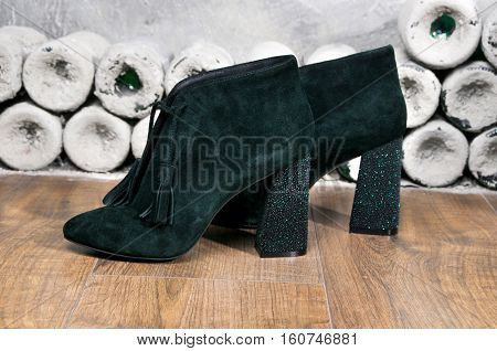 Pair suede shoe with high heels. Sexy Women's boots handmade on a background of antique bottles. Dark green ankle boots.