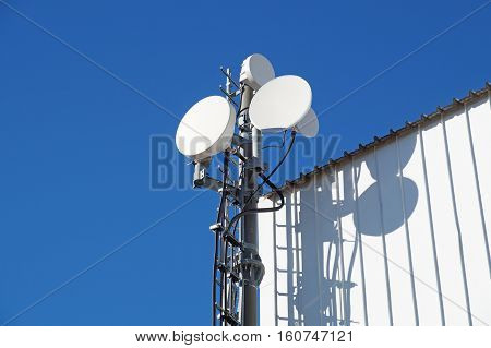 Telecommunication towers with TV antennas and satellite dish on clear blue sky,
