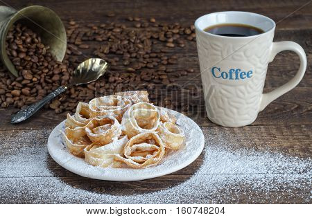 Crumbly cookies in powdered sugar and a Cup of coffee. Refried beans and spoon on a wooden surface.