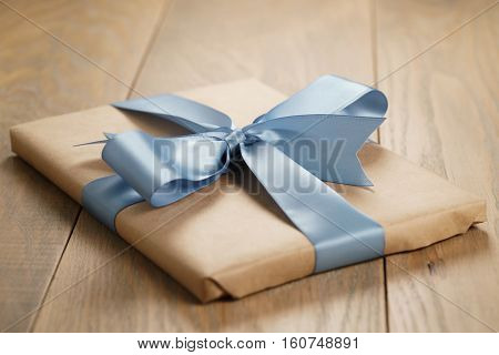 handmade gift brown paper box with blue ribbon bow on wood table, shallow focus