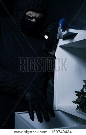 Thief Reaching Towards Drawer
