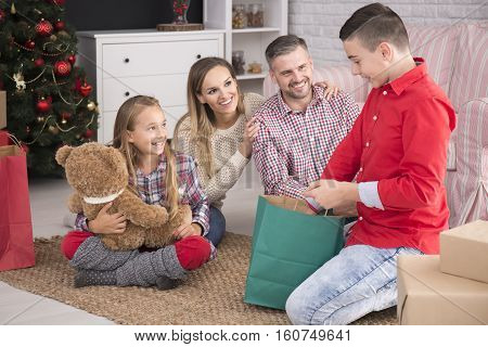Happy parents looking at their children unpacking Christmas gifts