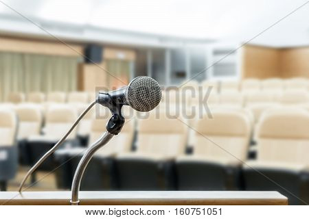 Microphone stand on podium with abstract blur photo of conference hall or seminar room in background. Business seminar concept.