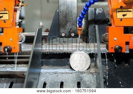 Band saw machine cutting tool steel bar by automatic feed working in factory. Closeup at machine.