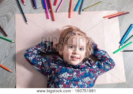 Child lying on the floor on paper looking at the camera near crayons. Little girl painting drawing. Top view. Creativity concept.