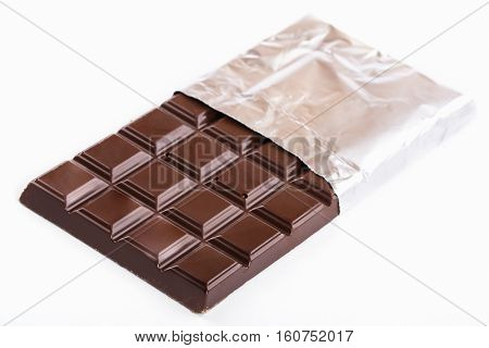 bar of dark chocolate in foil on a white background