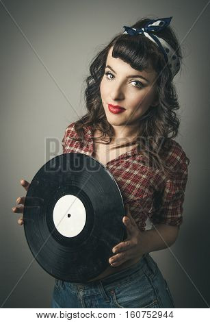 Cute retro pin up girl with a vintage hairstyle in ringlets and bandanna in her hair standing holding a vinyl record in her hands smiling at the camera in a beauty portrait