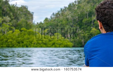 Traveler looking into Mangrove Jungle near Warikaf Homestay, Kabui Bay and Passage. Gam Island, West Papuan, Raja Ampat, Indonesia.