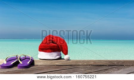 Christmas hat and flip flops on wooden jetty with tropical background
