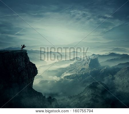 Young man riding a wild horse on the peak of a cliff. New lands discovery adventure and friendship concept.