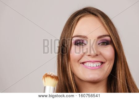 Woman Applying Loose Powder With Brush To Her Face