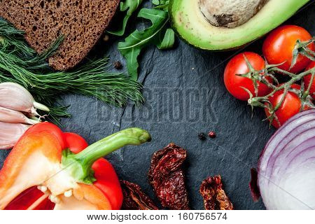 Snack ingredients: bread avocado arugula tomatoes garlic peppers sun-dried tomatoes on black stone background with a copy space in the center