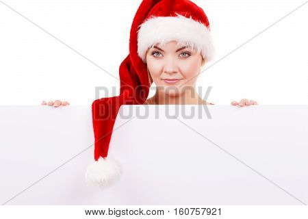 Woman holding blank empty board banner. Happy glad girl in santa claus helper hat. Christmas advertisement copyspace.
