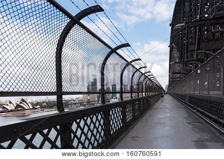 People walking and running on the popular pedestrian walkway on the Sydney Harbour Bridge in Australia
