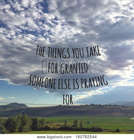 Inspirational quote.The things you take for granted someone else is praying for. Big cloud and blue sky over mountains and lush green farm field in summer.  Sunshine behind clouds. Instagram effects.