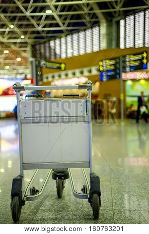 Empty metal cart for luggage standing at airport. Travel concept. Nobody. Vertical composition.