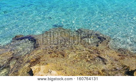 Bright turquoise sea water and coastal rocks nature background