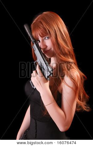 Attractive red girl with gun on black background