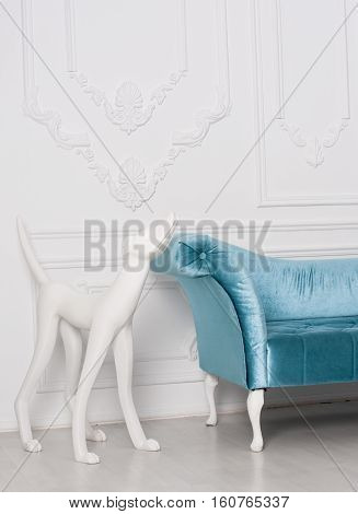 sofa armrest with white sculpture of dog against the wall