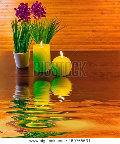 Green spa concept with candles and flowers and reflection