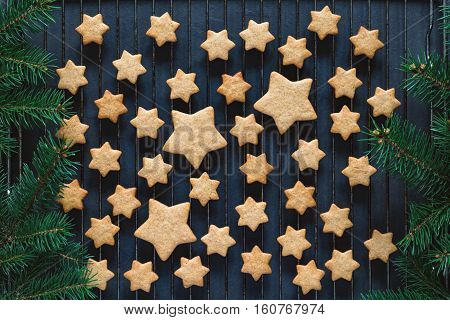 Stars shaped gingerbread cookies for Christmas on cooling rack. Holiday baking. Top view, toned image