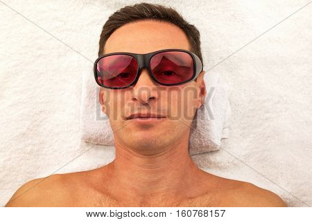 Relaxing handsome man with glasses in spa salon laying on white towel
