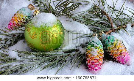 The green Christmas balls on a snow-covered branch. Christmas tree. Apperance toy with frost and snowflakes.