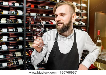 Sommelier checking wine quality in front of the shelves with wine bottles at the luxury supermarket or restaurant