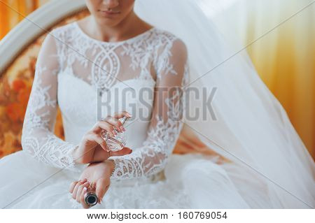 beautiful bride applying perfume on her wrist
