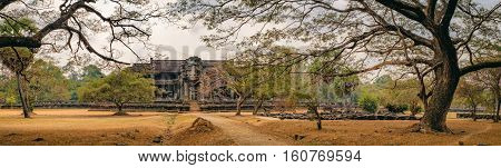 Ancient ruins of temple complex Angkor Wat surrounded by old tropical trees, Siem Reap, Cambodia. Angkor was the capital of Khmer Empire for over 600 years.