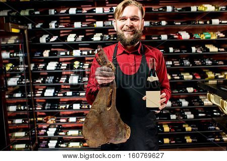 Portrait of a seller with wine bottle and jerked leg at the luxury supermarket. Choosing wine according to the type of meat. Bottle with empty label to copy paste