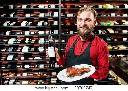 Portrait of a seller or sommelier with wine bottle and steak on the plate at the luxury supermarket or restaurant. Choosing wine according to the type of meat. Bottle with empty label to copy paste