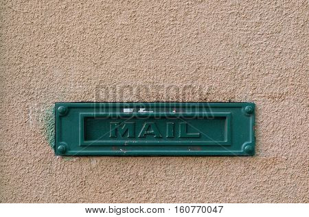 Green mailbox on the facade of a house