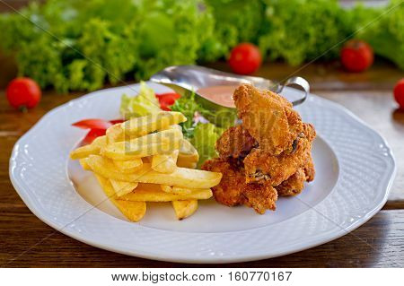 grilled chicken wings with spicy tomato sauce and potatoes fries in white plate with herb and tomatoes in background