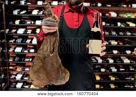 Food seller holding wine bottle and jerked leg at the luxury supermarket. Choosing wine according to the type of meat. Bottle with empty label to copy paste