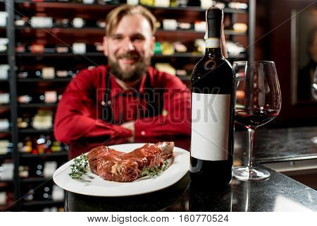 Meat steak with red wine on the table with man on the background in the restaurant or food market. Bottle with empty label to copy paste