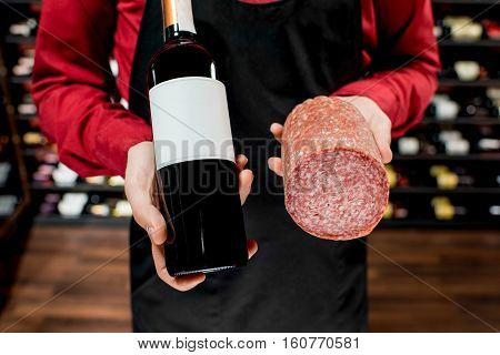 Food seller holding wine bottle and salamy sausage at the luxury supermarket or restaurant. Choosing wine according to the type of meat. Bottle with empty label to copy paste