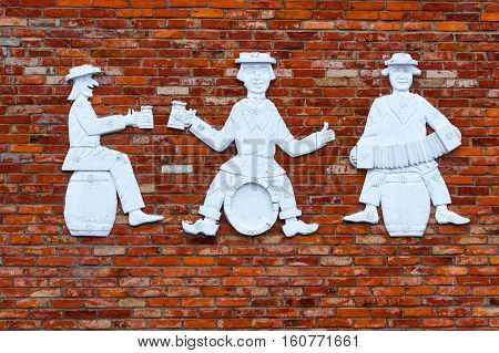 Stone figures of three men on brick wall. Humorous people are sitting on barrels drinking beer and playing harmonica. Lithuanian provincial countryside. Baltic rustic sculpture. Griezpelkiai Republic of Lithuania European Union