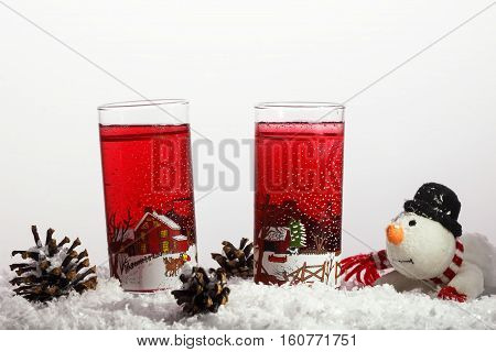 Cold juce in the glasses on the snow. Winter concept with snowman