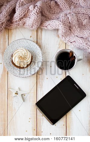 flat lay cupcake with coffee and tablet on wooden background framed by a knitted scarf
