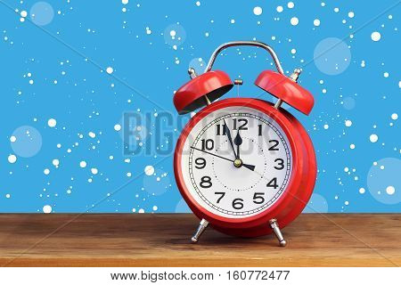 Red retro alarm clock at twelve o'clock amid flying snow. Midnight midday. Minutes about New year.