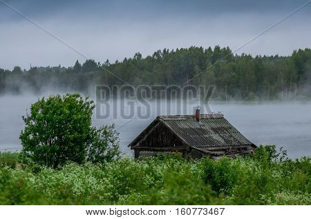 The traditional Russian log hut in poor condition on the bank of the river, early morning fog