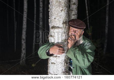 Portrait of sad senior man lost in birch forest