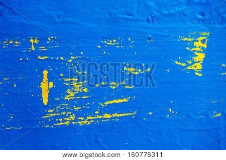 Painted wood texture with yellow and blue colors. Grunge texture of rough painted timber. Fresh blue paint over yellow. Bright shabby background. Abstract paint stains on wooden board closeup photo