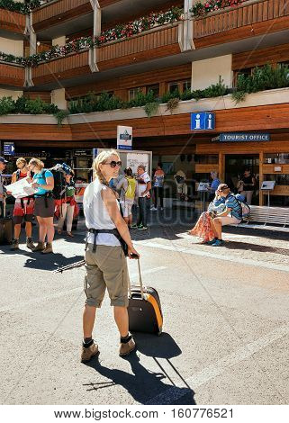 Young Woman With Luggage At Tourist Office Of Zermatt