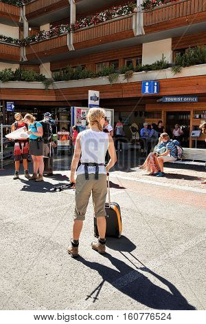 Young Woman With Luggage At Tourist Office In Zermatt
