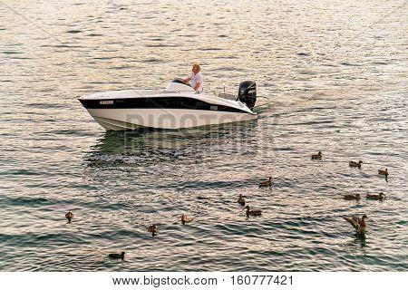 Man In Motor Boat At Pier In Ascona In Swiss