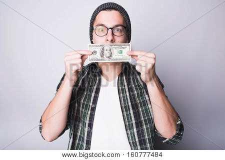 Man has money and he is satisfied. Guy is kissing 100 dollars banknote and making wish to have more